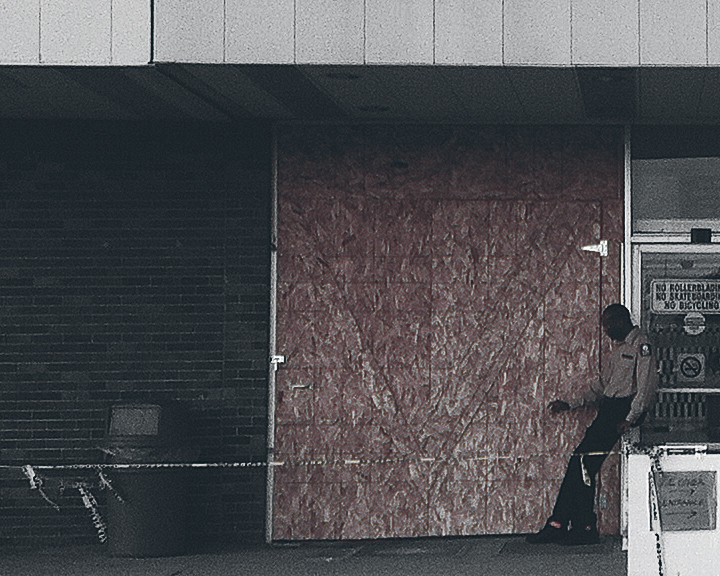 A security guard smokes a cigarette while guarding vacant Fort Richmond Plaza (©Deborah Clague)