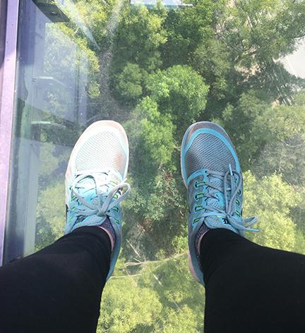 Looking down at Lantau Island—and my filthy Nikes—while looking through the glass-bottom gondola on Lantau Island, China (©Deborah Clague, 2018).