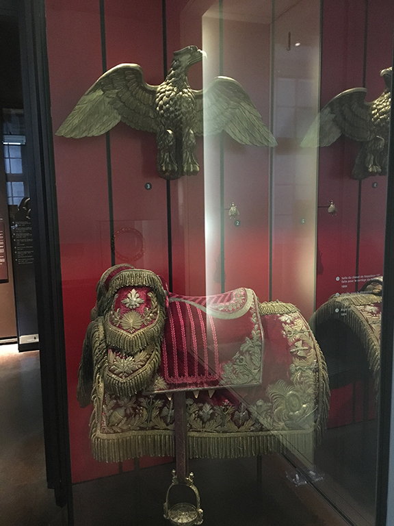 Napoleon's insignia included an eagle with outspread wings (represented here from a bronze gilt from the First Squadron of the Regiment of Mounted Grenadiers of the Imperial Guard) and the saddle used on Napoleon's horse during his coronation, Les Invalides (©Deborah Clague, 2019).