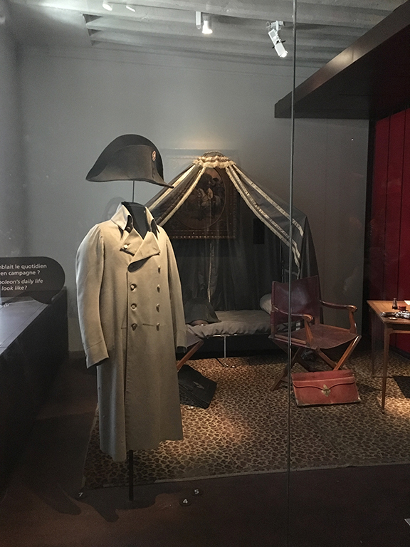 Napoleon's campaign clothing and furniture, including the cot where he slept, Les Invalides (©Deborah Clague, 2019).