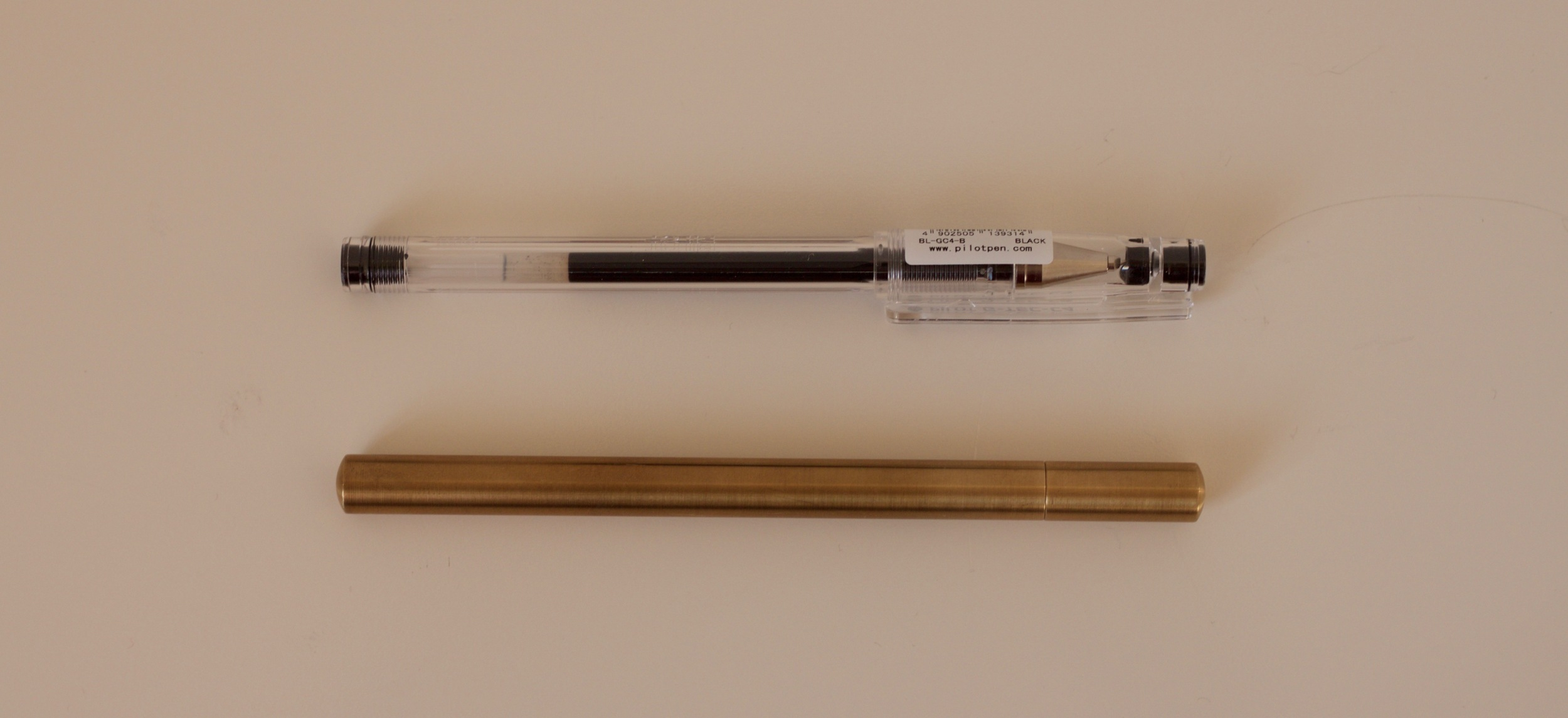 The Pilot Hi-Tec-C in it's standard housing compared to the Ateleia Brass Pen