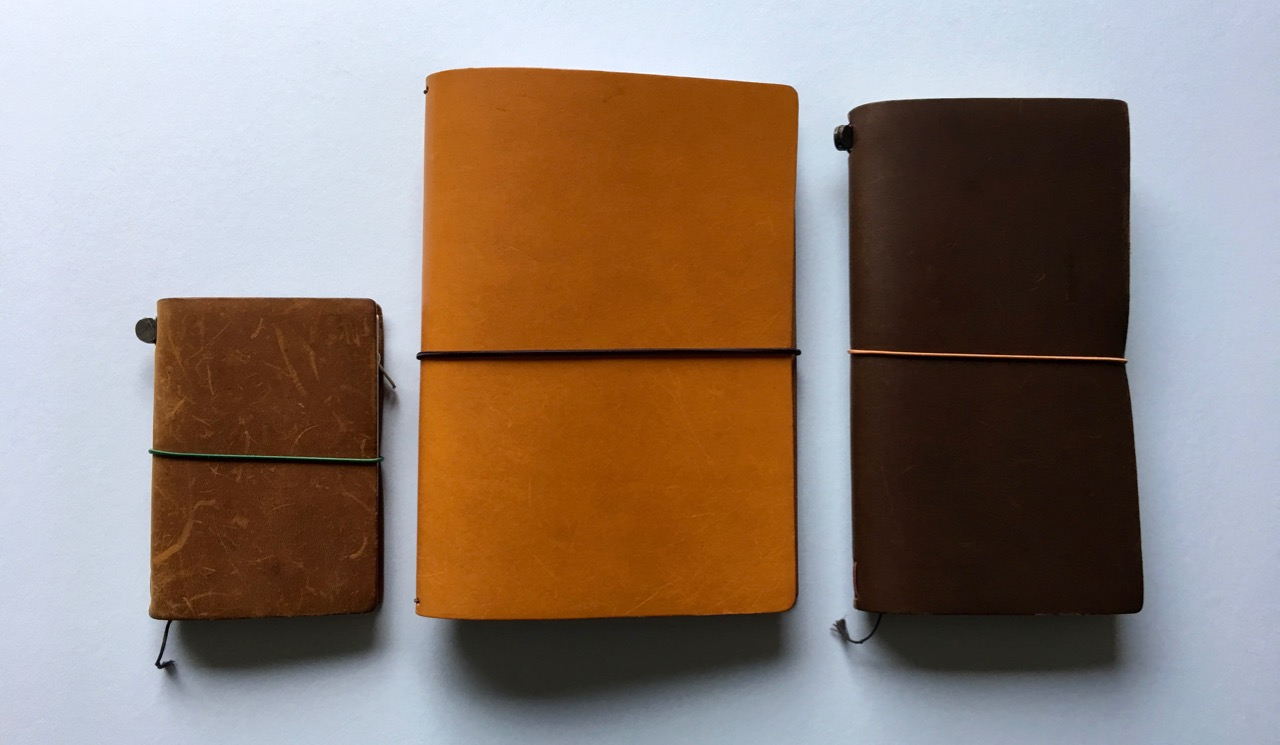 Comparisons against the Travelers Notebook, left the passport size in Camel, right the regular size in Brown. This also shows how thick the elastic is on the Start Bay cover.