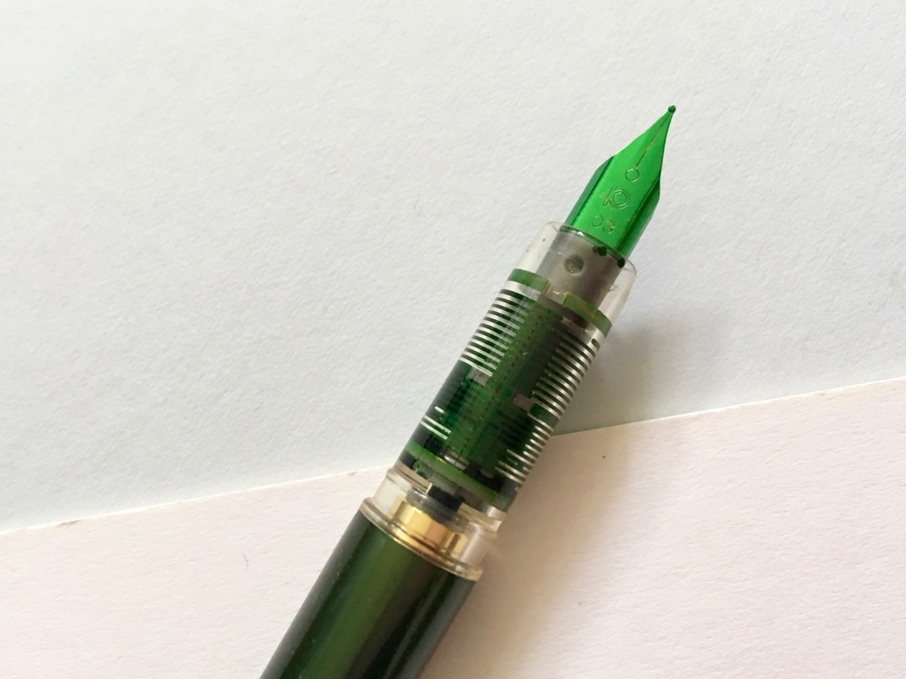 The luminous green nib and the clear plastic grip section.