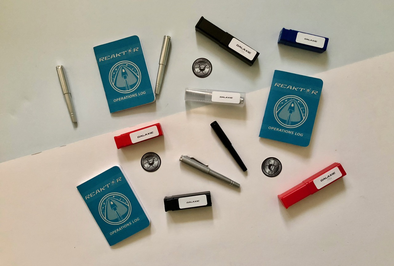 Everything that makes up the Reaktor line of pens: Galaxie pen, packaging, notebooks and stickers