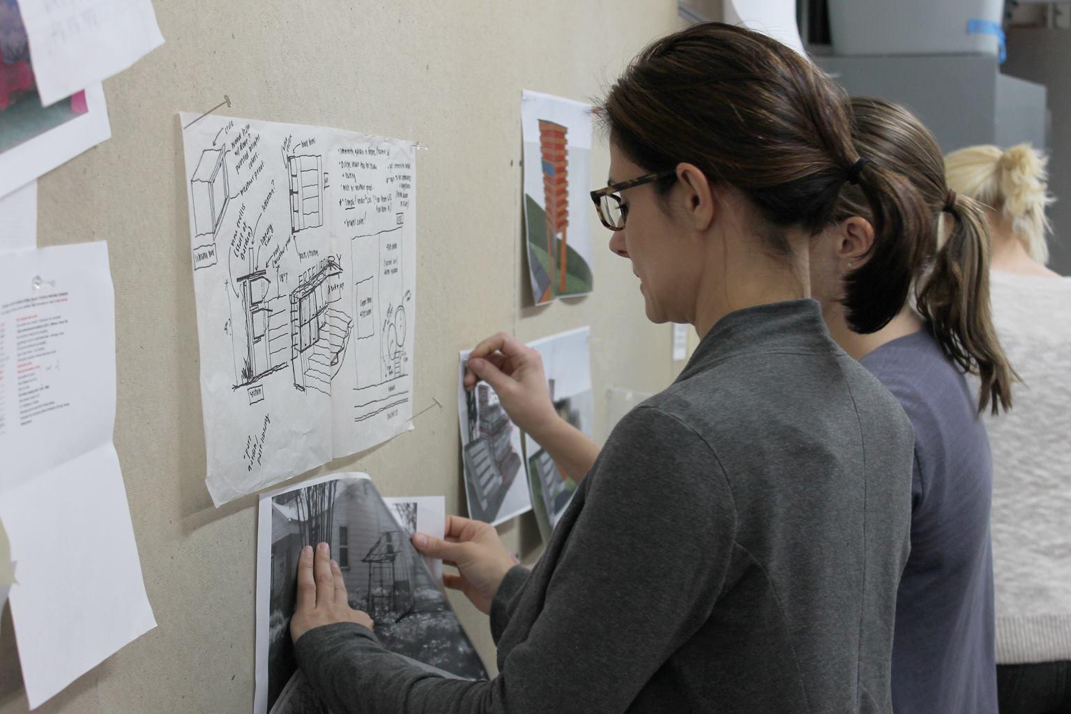 Studio Outside team members Allison Baker, Jessica Pfeffer, and Amanda Frey pin up inital sketches at a designer charette hosted by bcWorkshop. Image by bcWorkshop.