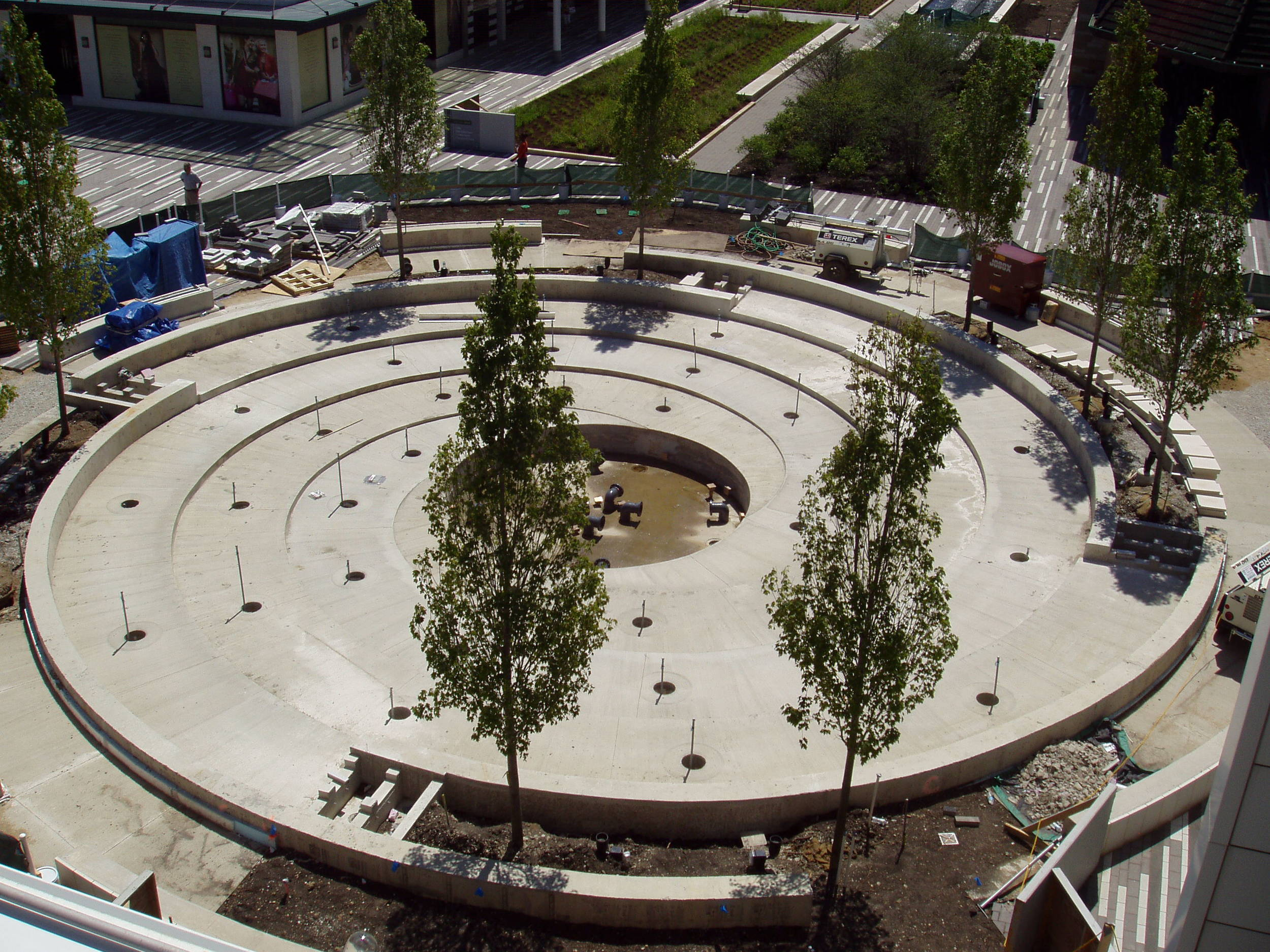 The concrete basin is cured.  A dozen ornamental trees are planted in perimeter planters along the fountain walls.  To the side of the planters are the weirs that supply water to the fountain.  Pipe connections for the jets are stubbed up.
