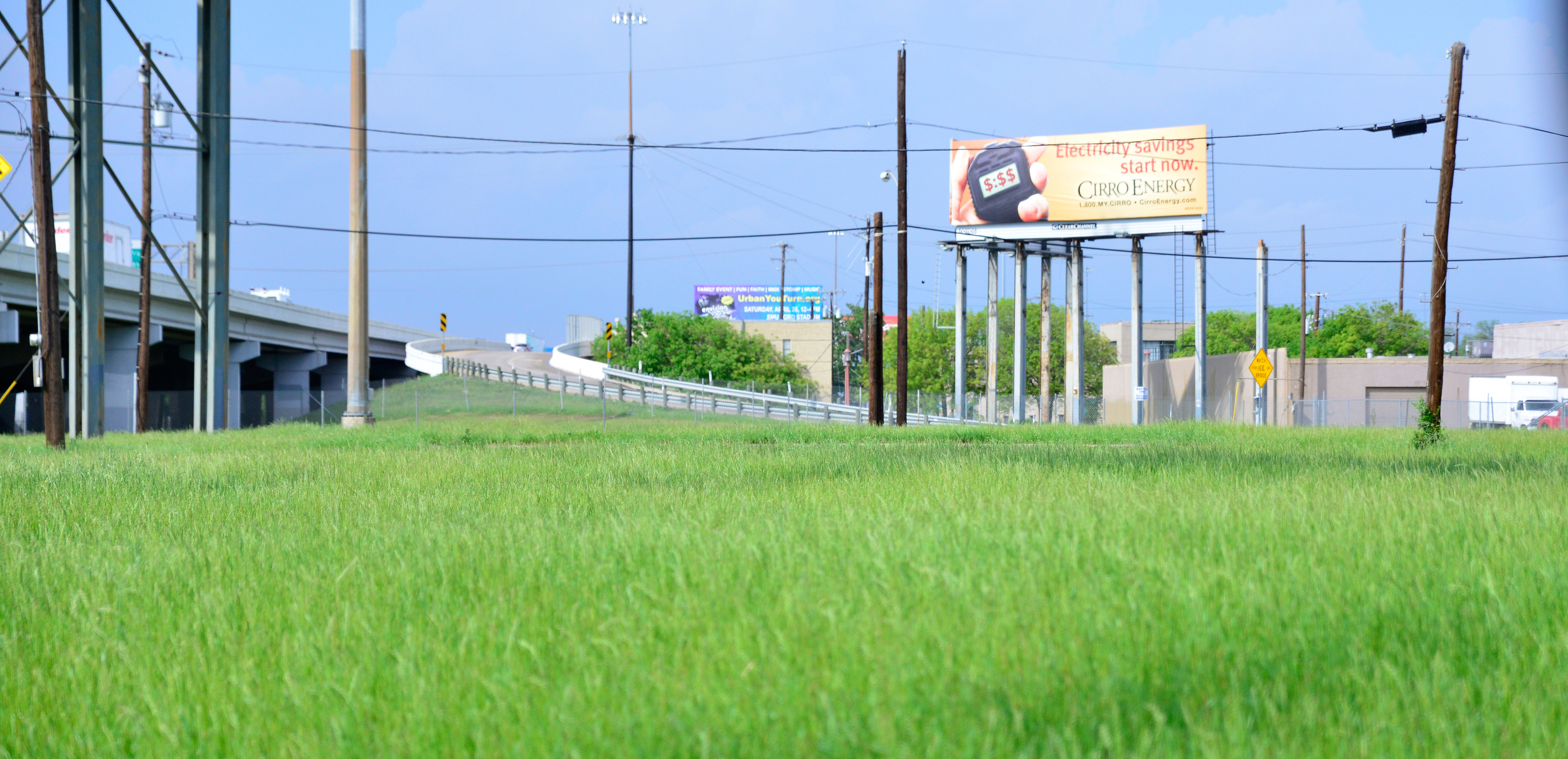 Looking across an urban meadow to the East bound entrance of I-30.