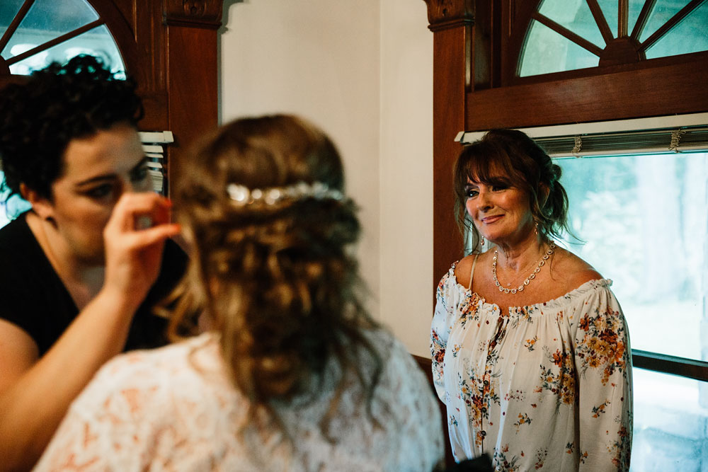mother of bride watches daughter get ready for her wedding day