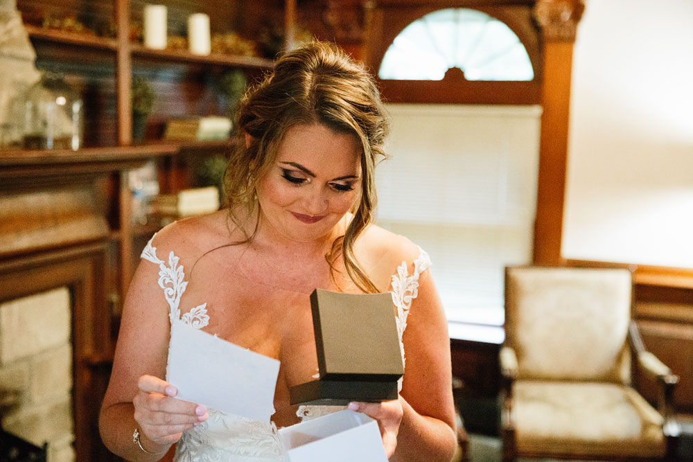 bride opening gift from her groom