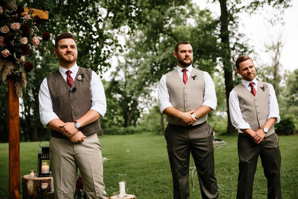 groomsmen and groom wait for bride