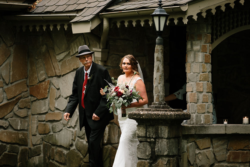 bride and father walk towards groom