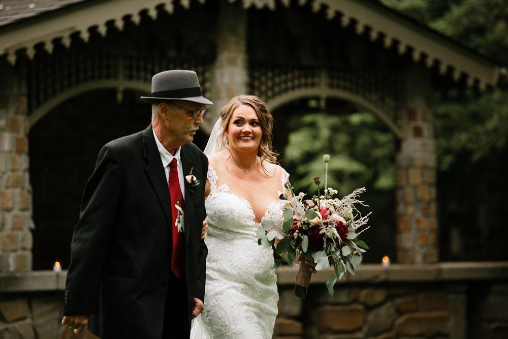 father and bride walk down isle
