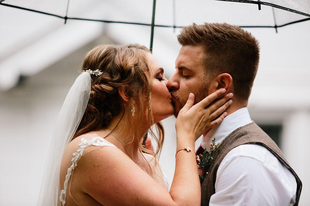 bride and groom kiss under umbrella during rainy wedding day