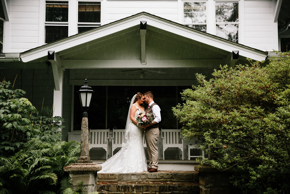 bride and groom stand on front porch