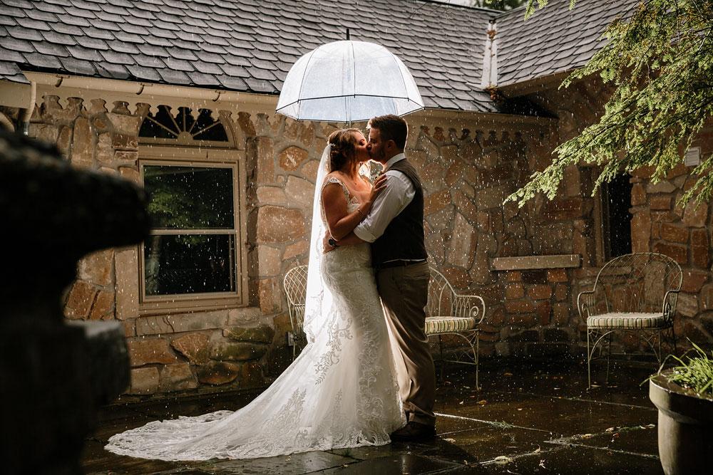 groom kisses bride under umbrella on their rainy wedding day