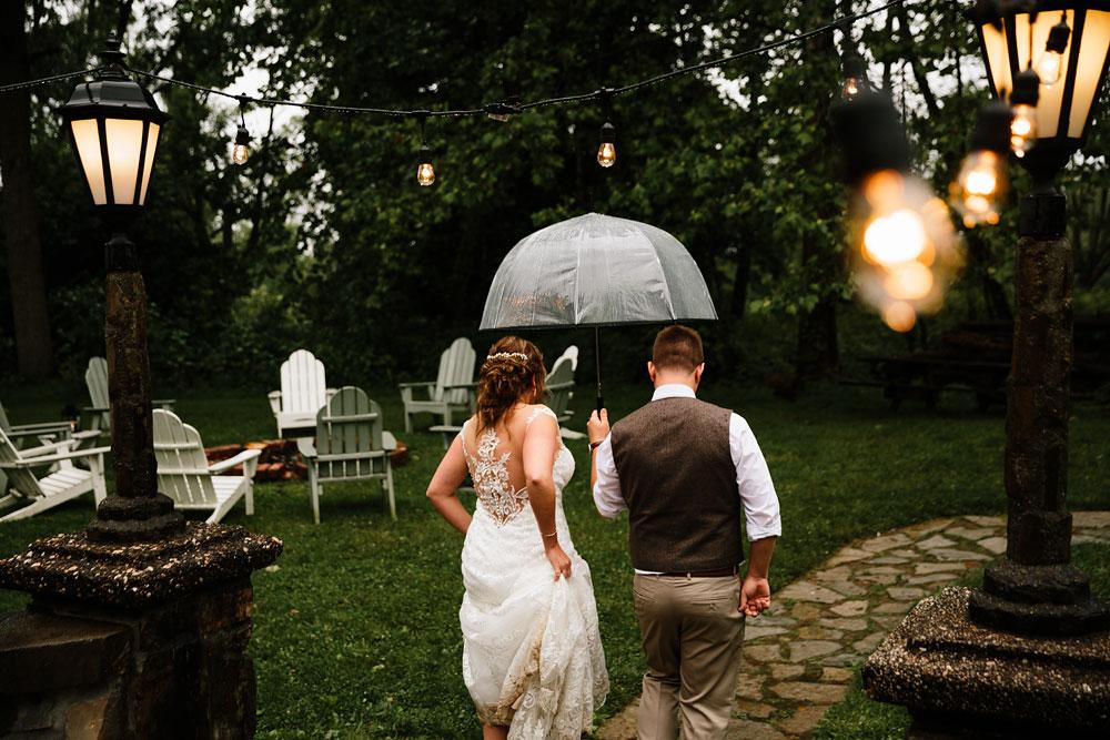 bride and groom walk away under umbrella