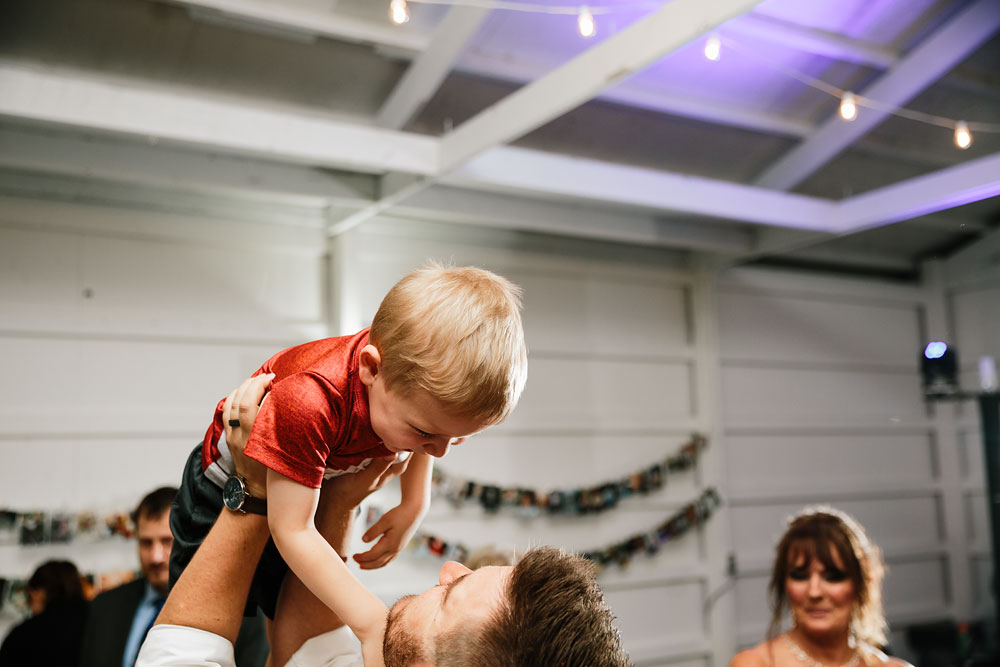 groom lifts up little boy at reception during dance