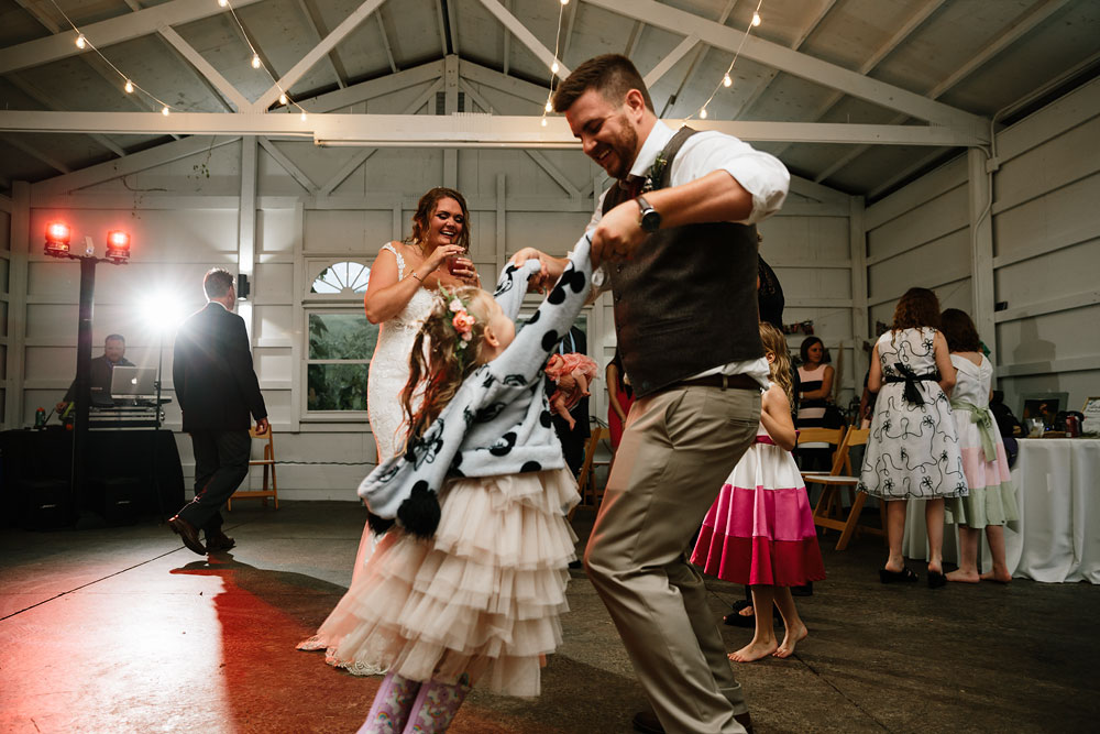 groom dances with little girl at reception