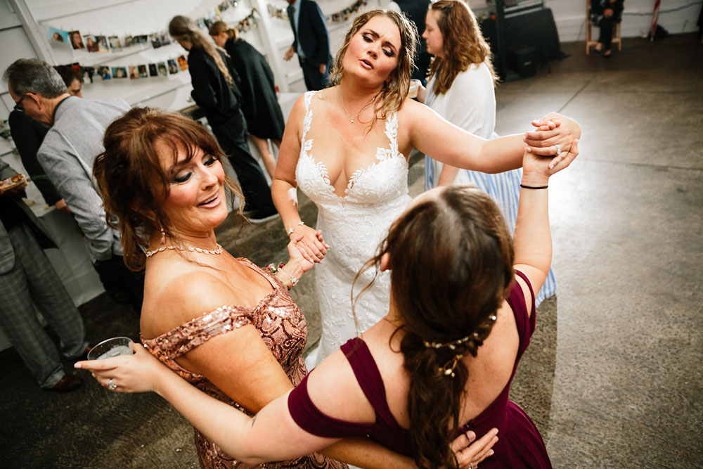 bride dances with mother and bridesmaid