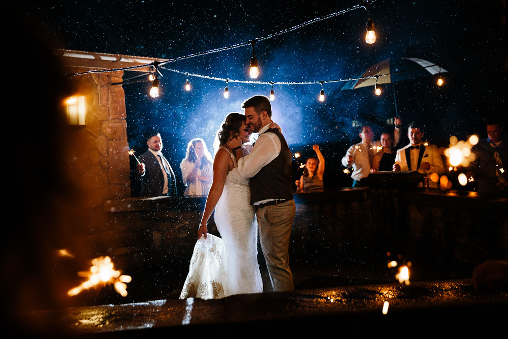 bride and groom dance in the rain