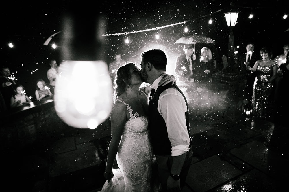 bride and groom kiss in the rain at wedding reception at Hines Hill Conference Center in Beautiful Cuyahoga Valley National Park