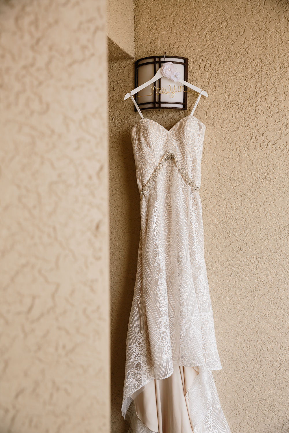 lacey wedding dress hanging against wall