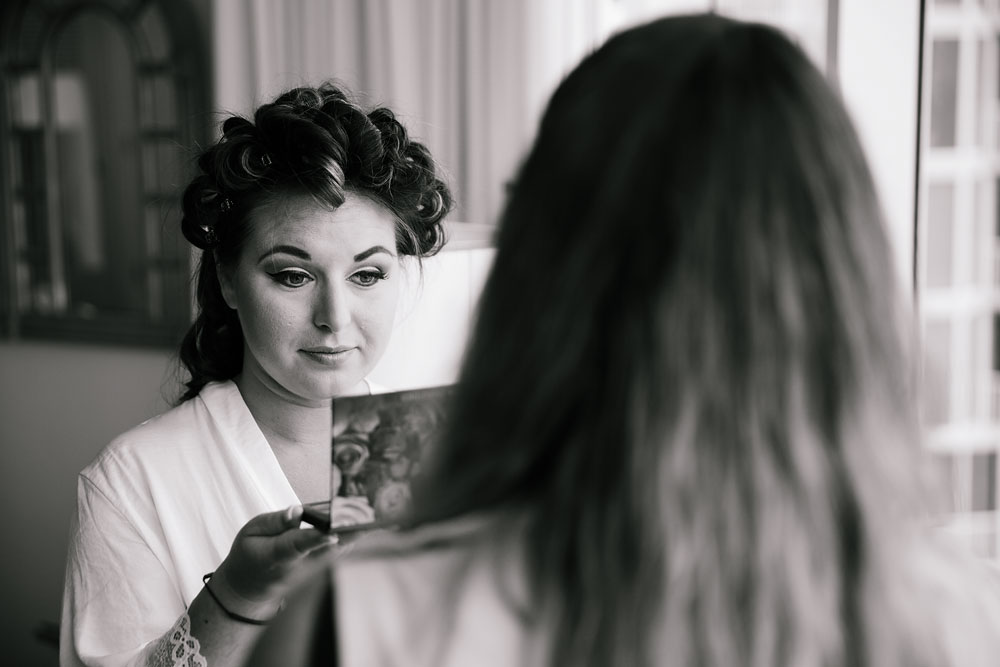 bride looking at herself in mirror before wedding