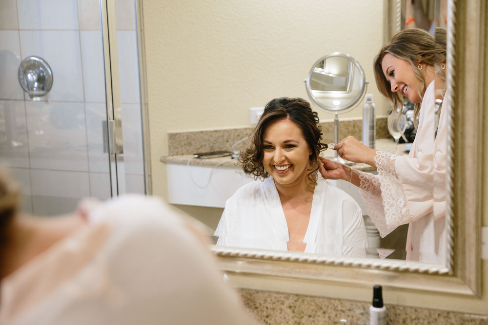 bride getting hair done before wedding smiling