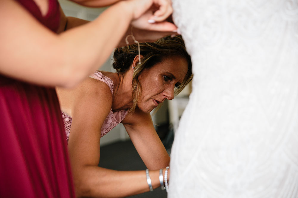 mother of bride helping bride fix dress before wedding
