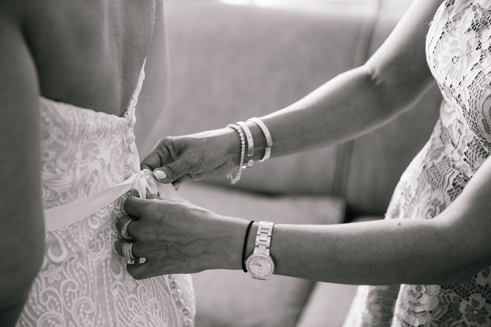 white wedding dress being tied with a bow