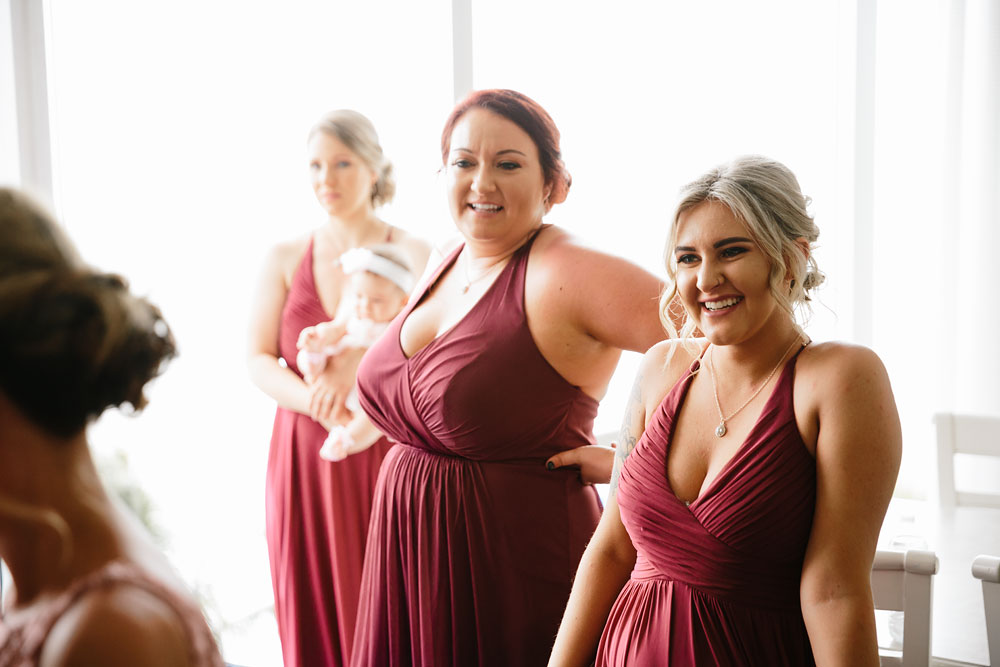 bridal party smiling in red dresses