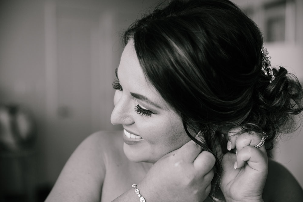 bride putting on earring before wedding
