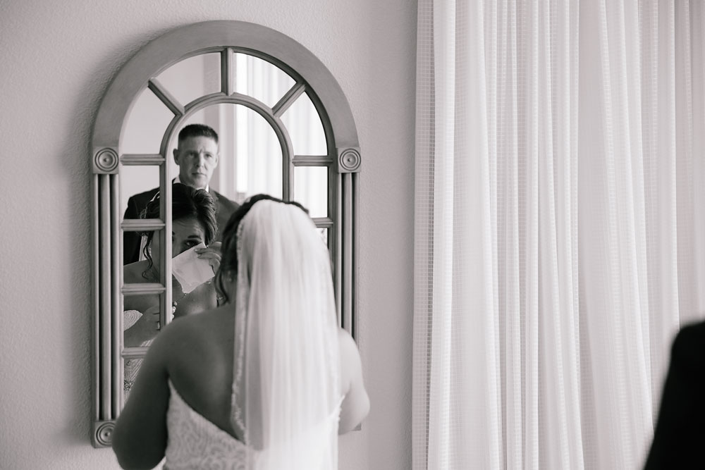 father looking at daughter through mirror before her wedding