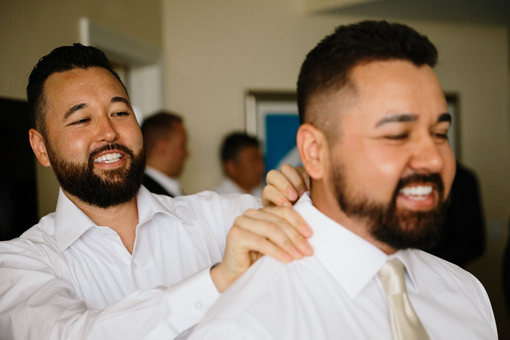 groomsman helping groom get ready for wedding