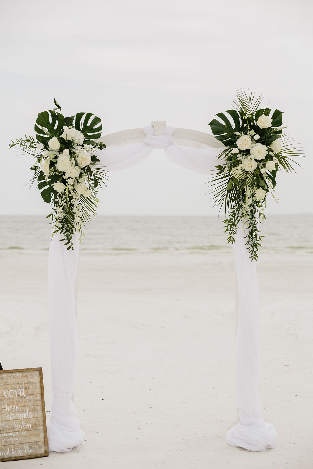 white archway at wedding on beach