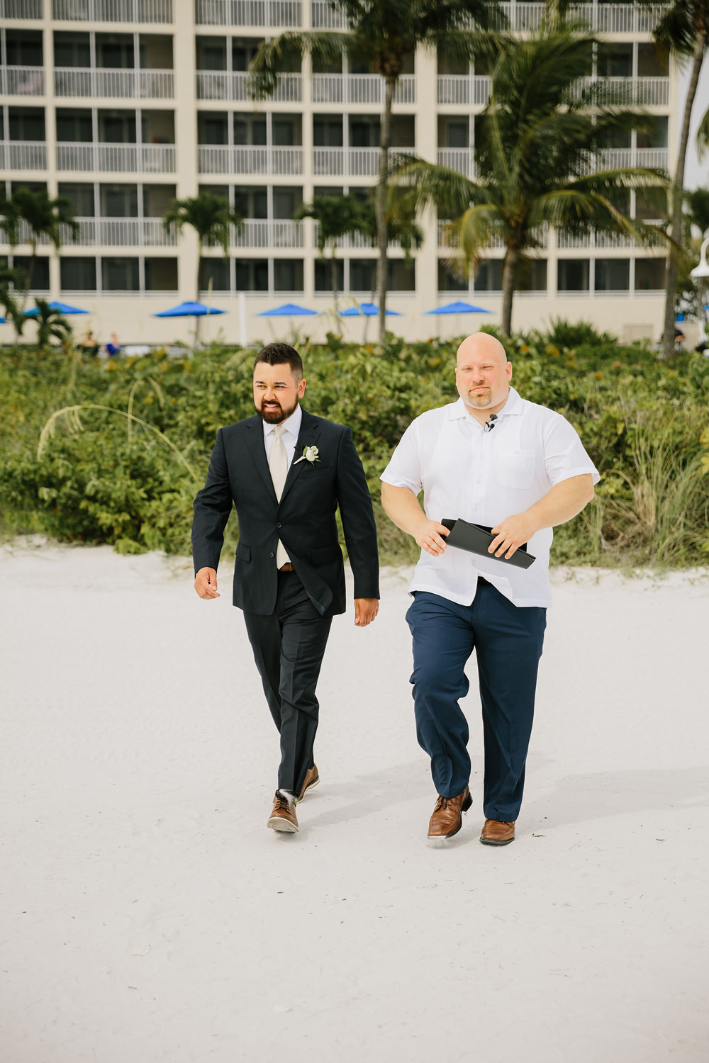 groom walking to meet his bride on beach for wedding