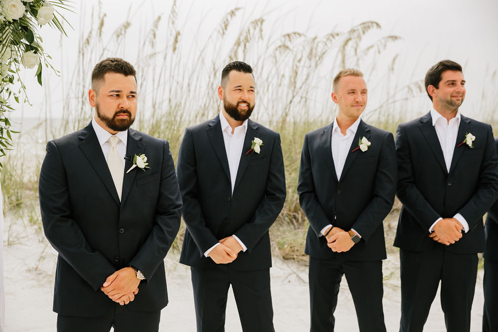 groomsmen and groom watching bride walk down the beach