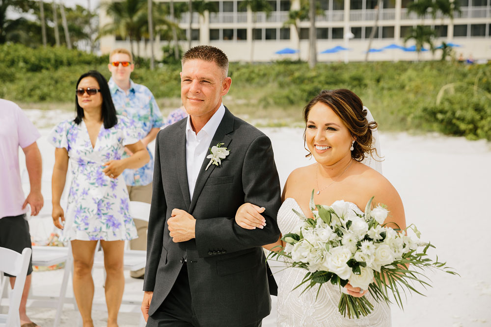 bride and father walking down isle on beach
