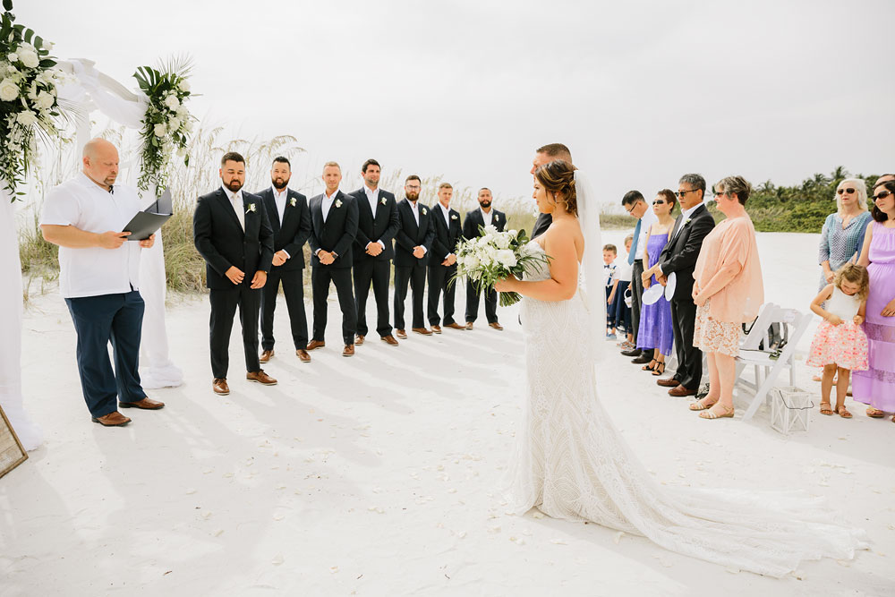 bride walking down isle on beach with groomsmen