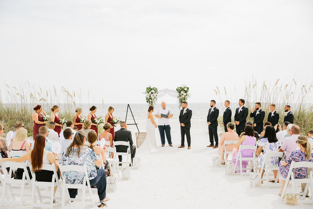 bride and groom standing at altar archway in front of  ocean on the beach