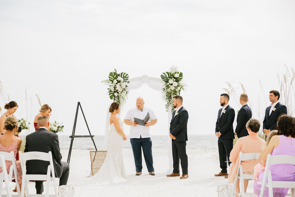 bride and groom standing at altar archway in front of ocean on beach