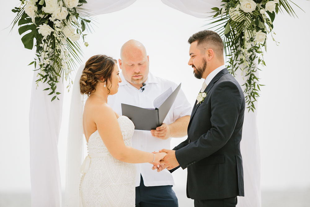 bride and groom standing at altar holding hands