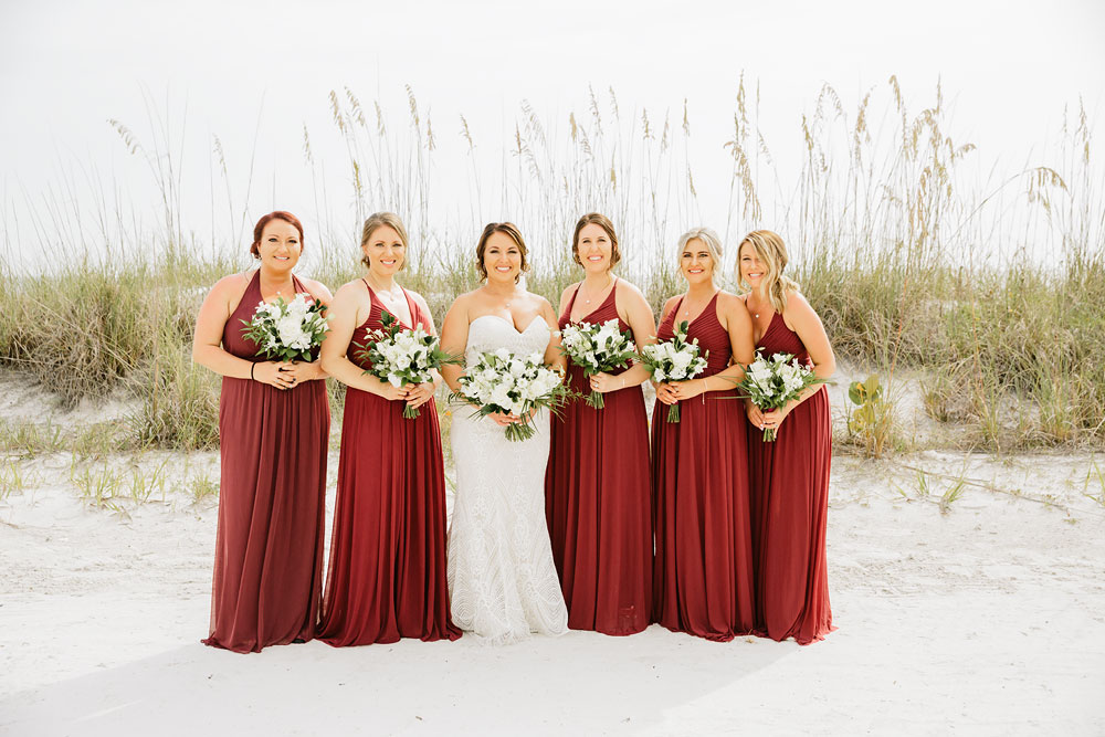 bride and her bridesmaids standing on beach