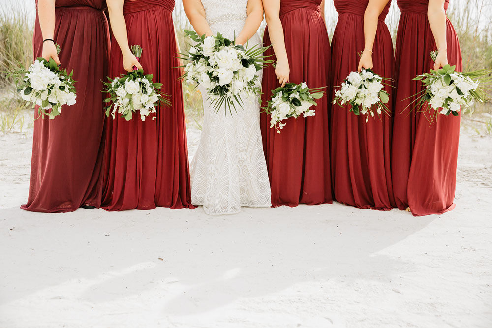 bride and bridesmaids standing on beach white red and green