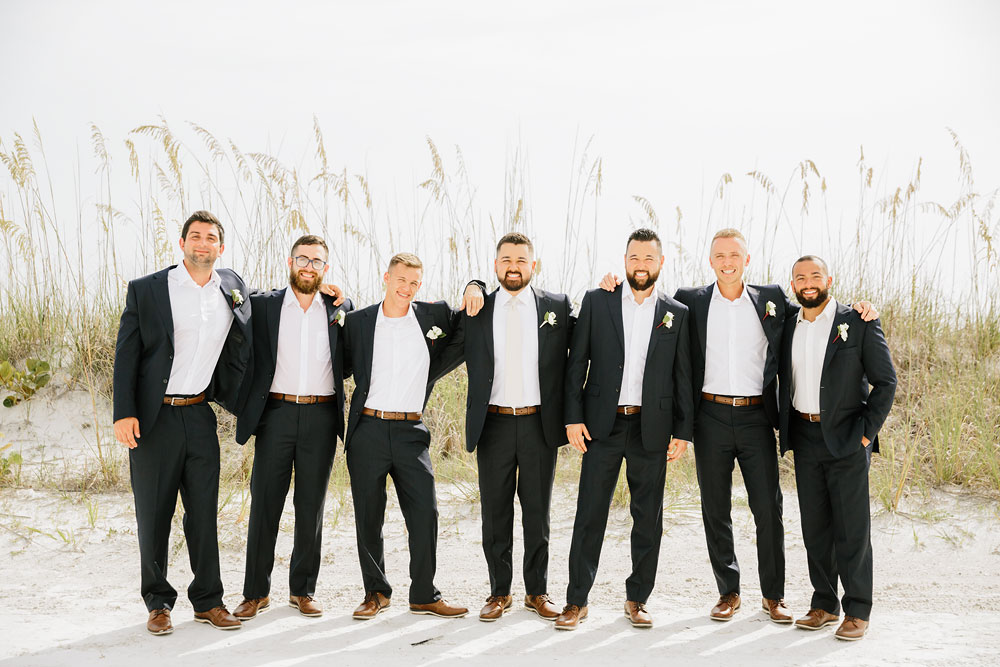 groomsmen and groom standing on the beach at destination wedding  at Pink Shell Resort in Fort Myers Beach, FL