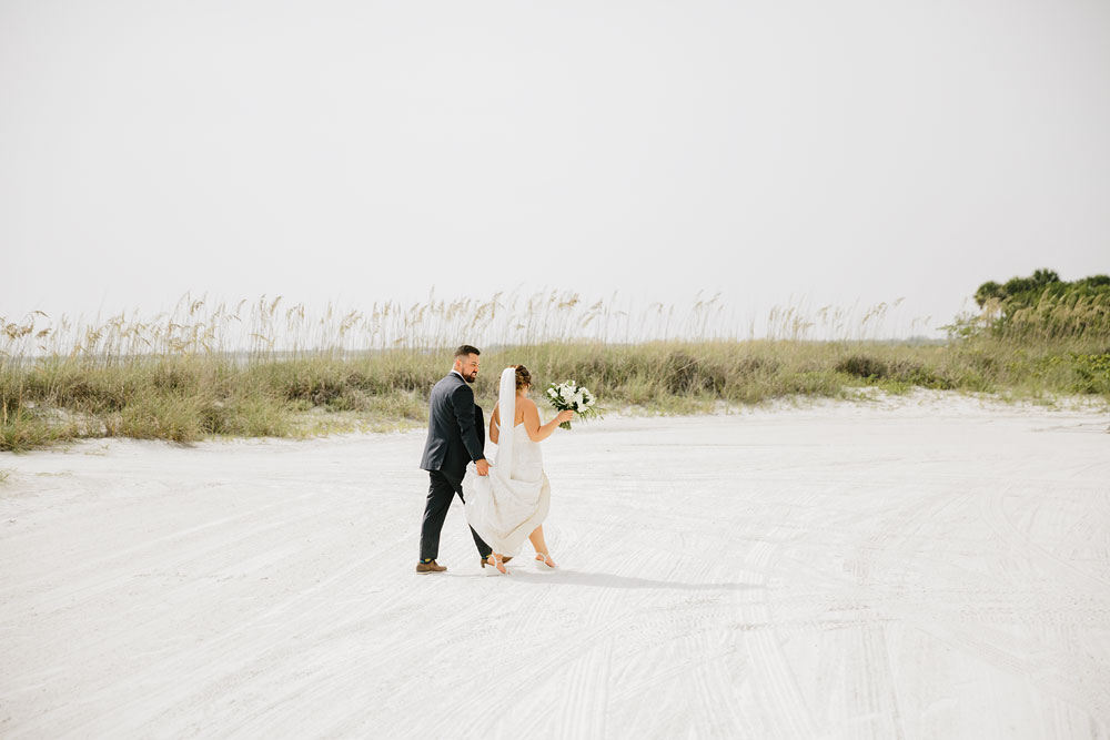 bride and groom walking away at destination wedding  at Pink Shell Resort in Fort Myers Beach, FL