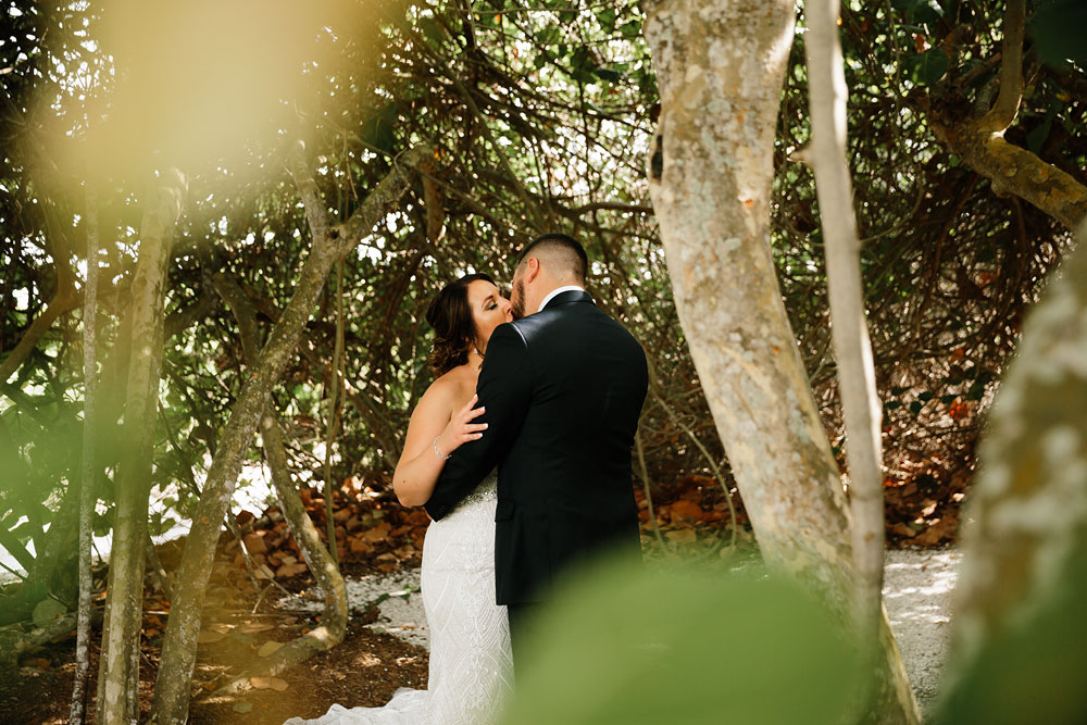 bride and groom kiss in woods near beach