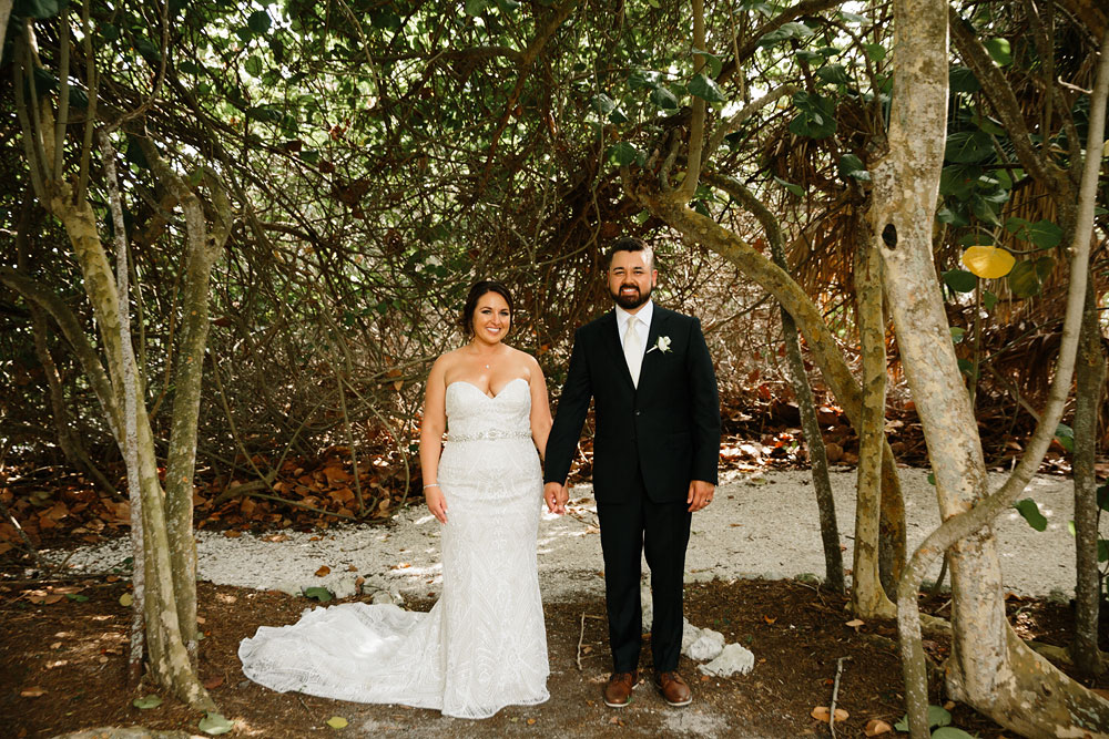 bride and groom standing in woods near beach