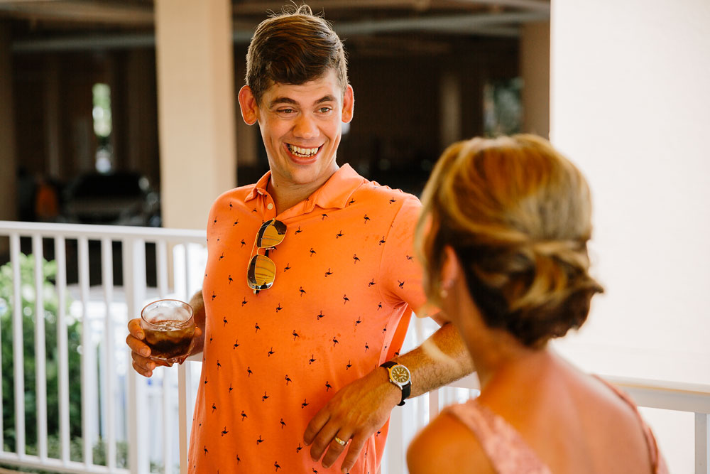 guy in orange shirt drinking at wedding reception