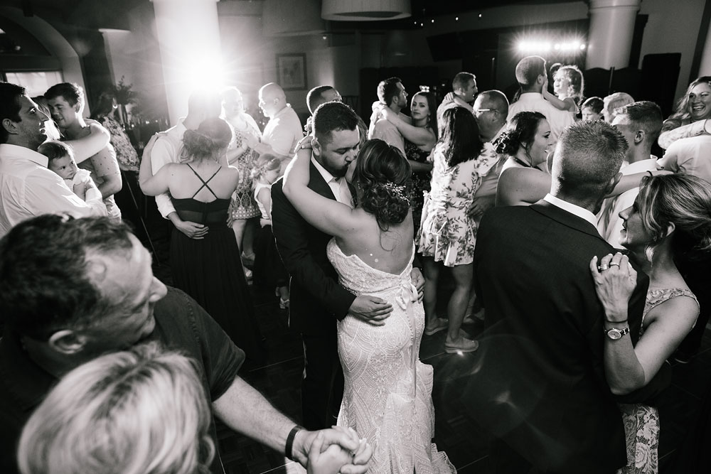 bride and groom kissing while dancing at reception